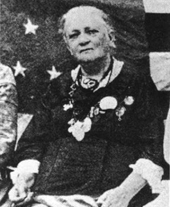 An elderly Cornelia Hancock dressed in black, sitting in front of an American flag