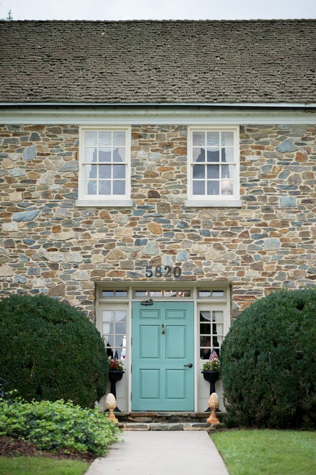 A turquoise door contrasts with stone walls of the Stone Manor