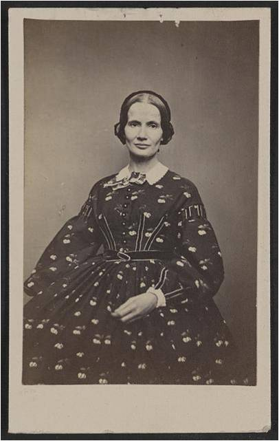 A 19th century woman poses for a black and white photo in a gown.