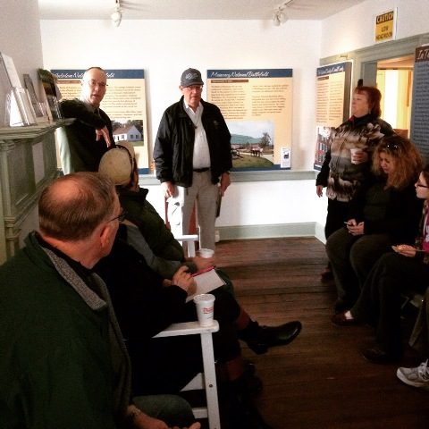 A group of volunteers sits in the historic Newcomer House listening to a park ranger speak.